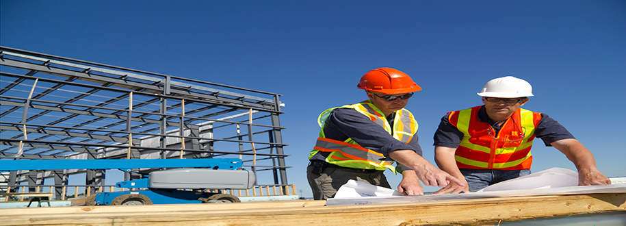 Image of construction workers reviewing blueprints