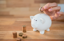 Grandfathered Plan Article Image - Hand placing money in Piggy Bank